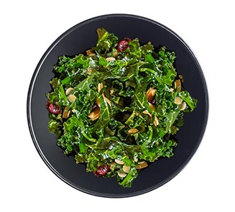 A bowl of cranberry almond kale salad.