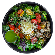 Beehive Kitchen's Lean Bowl, including tomatoes, broccoli, green beans, and mixed greens with a green dressing.